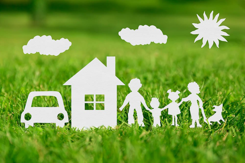 Cut Out of paper Family With House And Car On Green Grass